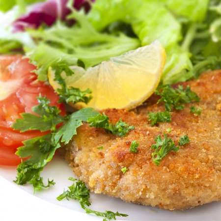 Schnitzel with salad, garnished with lemon and parsley.