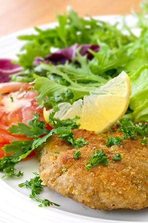 schnitzel: Schnitzel with salad, garnished with lemon and parsley.