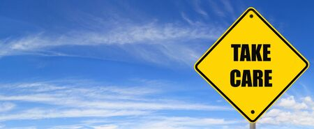 Road sign, against panoramic blue sky. Take care. Stock Photo