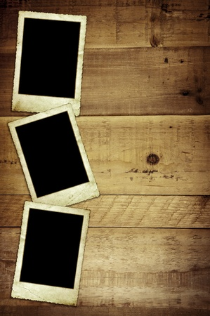 Old empty photo frames, over grunge wood background. photo