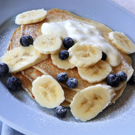 Pancakes topped with fresh blueberries, sliced banana and yogurt.   photo