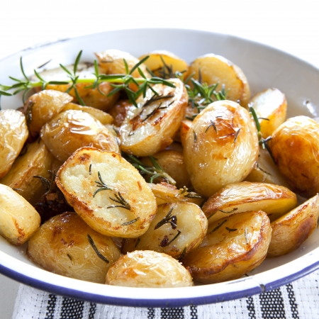 Roasted potatoes with rosemary, in old enamel bowl. Stock Photo