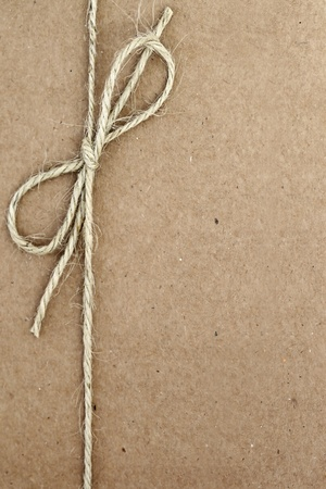 twine: String tied in a bow, over brown paper packaging. Stock Photo