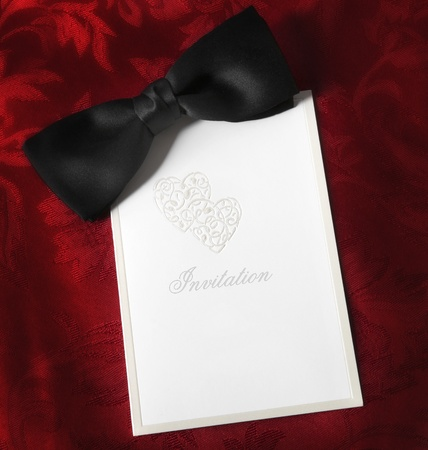 red tie: Invitation, with black bow tie over rich red brocade background.