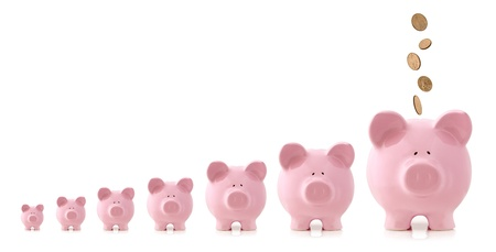 Pink piggy banks increasing in size, with coins falling into largest one.  Growing investment concept. Stock Photo
