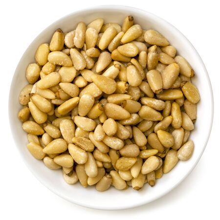 pine nuts: Pine nuts in small bowl, isolated on white background.  Overhead view. Stock Photo