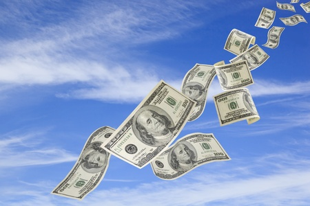 US one hundred dollar bills falling from a blue sky.