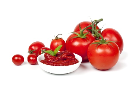 Tomatoes with a dish of tomato paste garnished with basil, over white background. photo