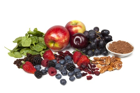 Foods rich in antioxidants, isolated on white.  Includes spinach, raisins, apples, plums, red grapes, cocoa powder, pecans, cranberries, strawberries, blueberries, raspberries and blackberries. photo