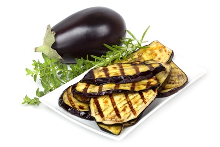 Grilled eggplant slices on a plate, with whole eggplant and fresh rosemary and oregano.