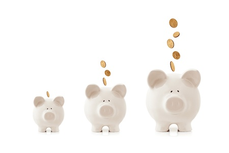 Piggy banks increasing in size, with coins falling into them.  Growing investment concept. photo