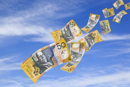 Australian fifty dollar bills falling from a blue sky. photo