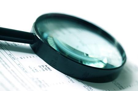 auditoría: Lupa sobre las cifras financieras. El enfoque suave, el tono azul verdoso. Foto de archivo