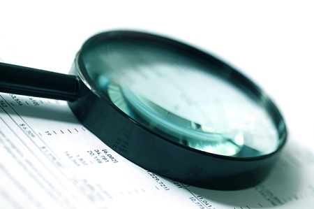 auditing: Magnifying glass over financial figures.  Soft focus, cyan tone. Stock Photo