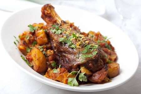 lamb shank: Lamb shank dinner, with vegetables, topped with parsley and lemon rind  Stock Photo