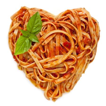 spaghetti: Spaghetti of fettucine in een hartvorm, met tomatensaus en basilicum, geïsoleerd op wit