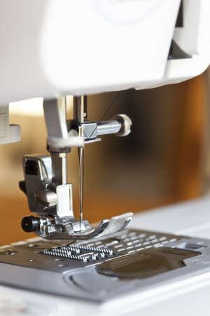differential focus: Close-up of modern sewing machine, with focus on needle   Blurred background