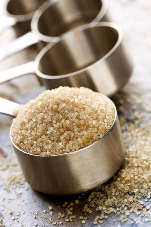 measuring spoons: Raw sugar overflowing a measuring spoon, over slate background