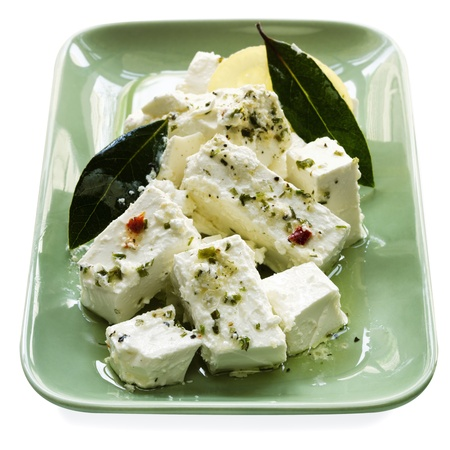 Dish of creamy marinated feta cheese with bay leaves and preserved lemon.  Isolated on white. photo