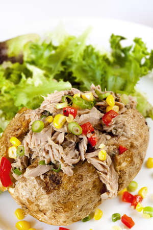 potato leaves: Baked potato with tuna, sweet corn, capsicum and shallots, served with salad. Stock Photo