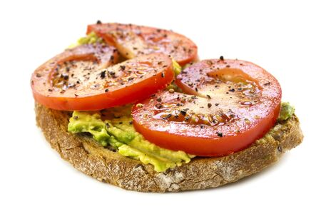 open topped: Open sandwich topped with avocado, tomato, and ground pepper   Isolated on white background