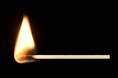 matchstick: Horizontal burning match isolated on black background
