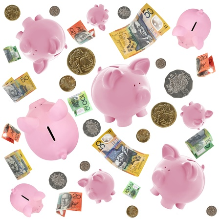 Piggy banks and Australian money falling over white background.   photo