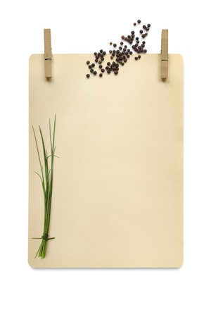 clothespegs: Cardboard hanging from clothespegs, isolated on white, with peppercorns and chives.  Food background with lots of copy space for any message or recipe.