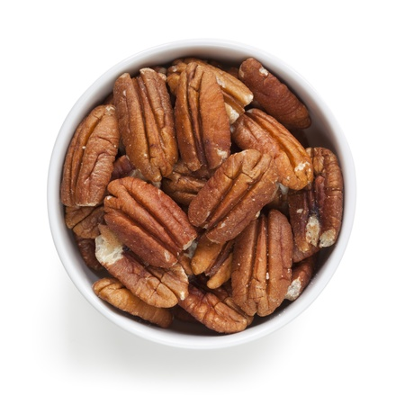 pecan: Pecans in small white bowl, isolated over white background.  Overhead view. Stock Photo