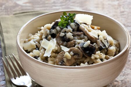 risotto: Bowl of mushroom risotto, garnished with thyme and parmesan.