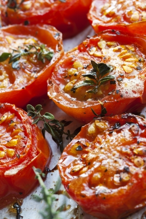 Roasted cherry tomatoes with herbs, on a baking tray straight from the oven  photo