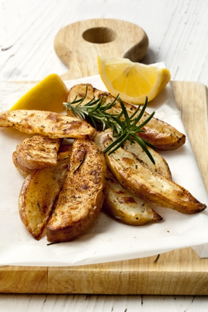 wedges: Oven baked potato wedges on a board, with fresh rosemary and lemon.