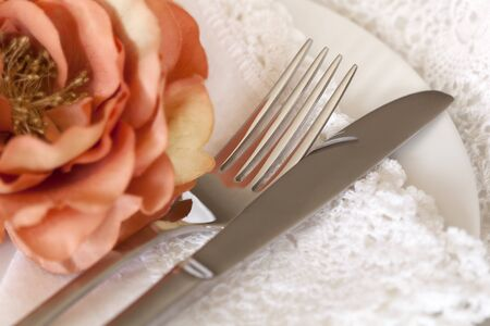Pretty place setting with peach flower and lace napkins. photo