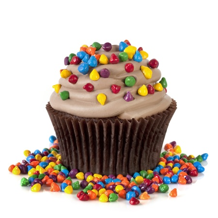 hundreds and thousands: Chocolate cupcake topped with colorful sprinkles.  Isolated on white.