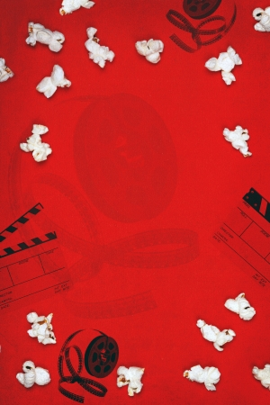 Red paper background with popcorn, film reel, and movie clapper   Lots of copy space  photo