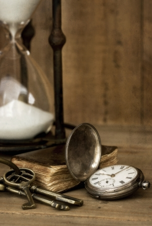 Vintage grunge still life with hour glass, pocket watch, old brass keys and tattered book