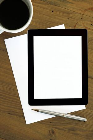 Digital tablet with white screen, over blank paper, with coffee cup and pen   Ready for your message  photo