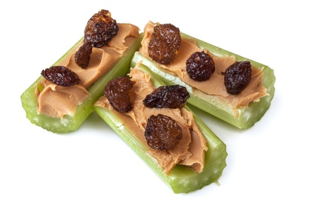 Ants on a log, celery with peanut butter and raisins, isolated on white   Healthy snacks  Stock Photo
