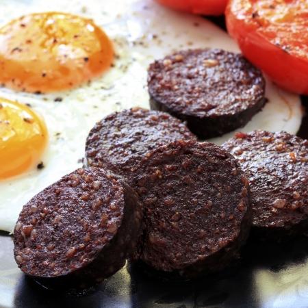 huevos estrellados: Desayuno de pud�n negro tradicional, huevos fritos y tomates