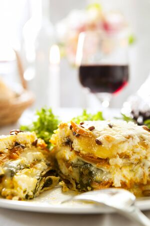 Vegetarian lasagne with salad and a glass of red wine  photo