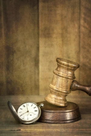 civil law: Time and justice concept   Old pocket watch with wooden gavel, with timber background   Added grunge effects