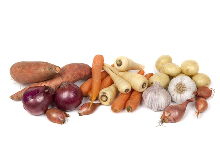 Variety of root vegetables isolated on white   Includes carrots, parsnips, red onions, shallots, garlic, potatoes, and sweet potatoes