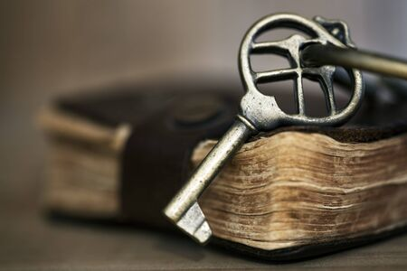 differential focus: Antique brass key on old leather-bound book   Shallow depth of field