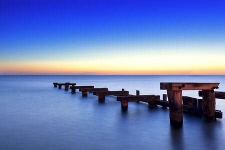 wooden dock: Old wooden jetty at sunset, over peaceful bay