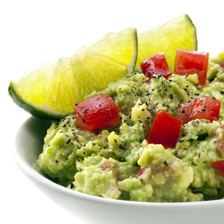 guacamole: Bowl of guacamole with lime wedges.  White Background.