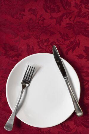 cubiertos de plata: Configuraci�n de lugar en rojo mantel brocado. Vista de arriba.