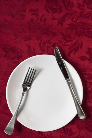 cutlery: Place setting on red brocade tablecloth.  Overhead view. Stock Photo