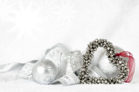 bell shaped: Heart-shaped Christmas bells over white, with baubles and ribbon on white fur  Stock Photo