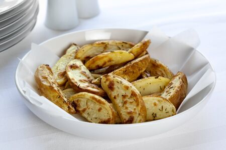 ovenbaked: Oven-baked potato wedges in white serving bowl, sprinkled with rosemary  Stock Photo