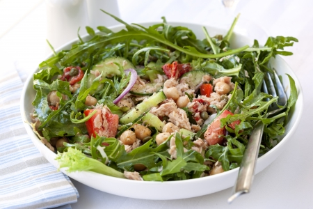 capers: Tuna salad with chickpeas, arugula, tomatoes, red onion and capers   Delicious, low-fat healthy eating  Stock Photo